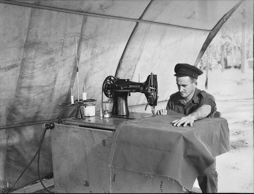 第110師団作業場のモーター・トリマー、名工A.R.ベネット。彼はオーストラリア人の電気技師兼機械技師で、頑丈なシンガー・ミシンを使って粗布袋(キャンバス・バッグ)を縫っています。