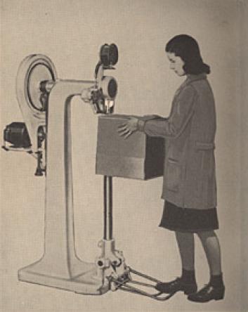 アイディール・ステッチャー社の段ボール底縫ミシンと女性